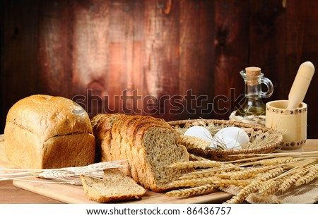 bread and wheat on the old wooden background