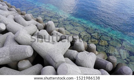 breakwater consisting of tetrapods in the turquoise blue water of the ocean. clear clear sea water off the coast of a tropical island #1521986138