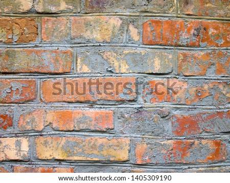 Brick wall of orange and yellow bricks. Rough masonry. Rough uneven surface. Background with copy space.