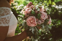 Bride holding her boho wedding flower bouquet. Perfect image for wedding style magazines and websites, copyspace, fashion, bohemian, flowers decoration businesses, florist and other related subjects.
