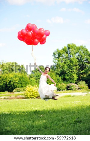 bride in  white dress with balloons  on  green field