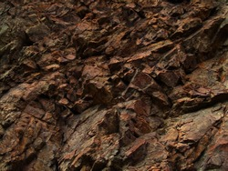 Bright red-brown stone background. Golden rock texture. Mountain close-up.   Mountain texture.
