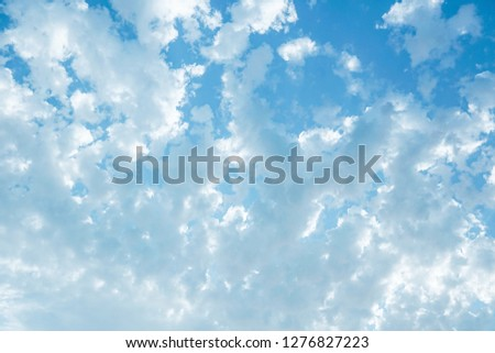 bright saturated blue sky, and a large cloud with rays of the sun.                               #1276827223