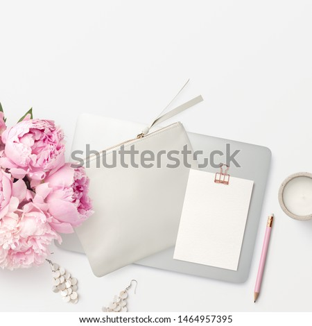 bright square home office background with closed laptop computer, bunch of fresh pink flowers, writing utensils, a candle and a blank notecard with rose gold paper clip and copyspace for a message