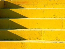 Brightly lit yellow concrete staircase, with shadows on the left side