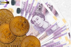 20 British pounds bills and golden bitcoins. Cryptocurrency investment concept. Crypto mining or trading