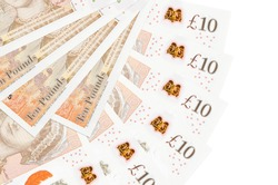10 British pounds bills lies isolated on white background with copy space stacked in fan shape close up