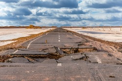 broken asphalt road with cloudy sky in the middle of the  Lut desert,hottest desert in the world, also known like Kalut Desert