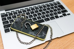 Broken smartphone and padlock placed on a personal computer