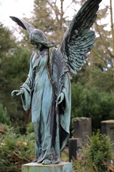 Bronze angel statue in a graveyard, green patina, oxidation