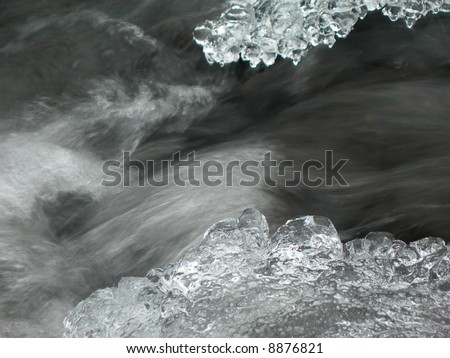 Brook is covered by ice and water flows under them with a small strem - stock photo