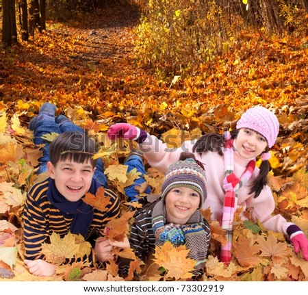 Brothers and sister playing outside in Autumn leaves.