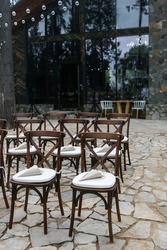 brown wooden chairs with crisscross back. White pillows on chairs and envelopes with white rose petals. against the backdrop of nature on a stone floor. holiday concept.