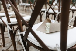 brown wooden chairs with crisscross backs close-up. White pillows on chairs and envelopes with white rose petals. against the backdrop of nature on a stone floor. holiday concept.