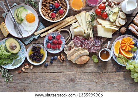 Brunch or breakfast set, meal variety with fried eggs, sausage and cheese variety, granola, smoothie, fruits and berries. Overhead view #1355999906