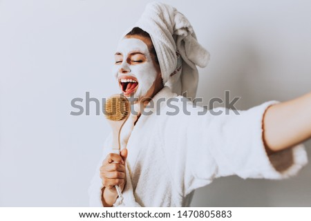 Brunette cute young girl female woman singing  with refreshing spa body care mask doing selfie in light room at home. Morning wake up / body care concept