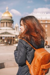 Brunette girl in jacket with fur hood is in the opposite direction from the camera and looking at St. Isaac's Cathedral and the main square in Saint-Petersburg Russia