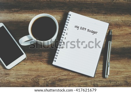 2017 budget list on notepad with smart phone, coffee and pen on a wooden table, retro style #417621679