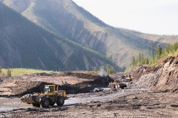 Bulldozers and wheel loaders at work. Mining. Bulldozers cut the topsoil in mountainous forested areas and wheel loaders transport the soil