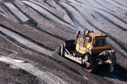 Bulldozers in mountainous wooded areas, layer by layer, remove mountain soil from the surface and shovel it to the side.