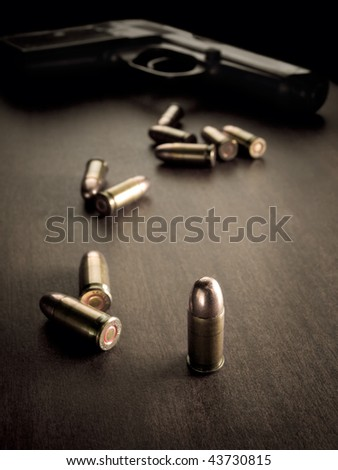bullets with handgun in the back of the scene with focus on the bullet,sepia toned, closeup with vignette, useful for various security,protection or criminal topics