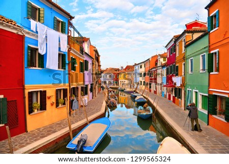 02.12.2018. Burano island picturesque street with small colored houses in row, windows, doors and water canal with fisherman boat. Venice Italy #1299565324