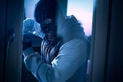 burglar with crowbar to break door to enter the house