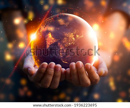 Burned Globe in hands with golden particles and flares