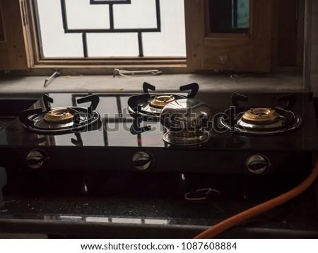 3 burner gas stove in kitchen #1087608884