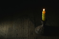 Burning candle on a antique candlestick in the dark