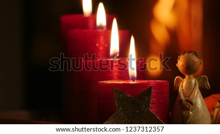 4 burning candles in darkness close-up with angel and cheminee fire in background