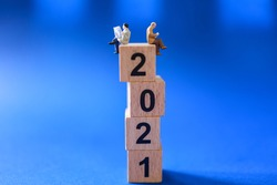 2021 Business and News Concept. Two businessman miniature figures people sitting and reading newspaper and book on stack of wooden number block with blue background.