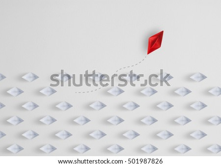 Shutterstock  Business concept  as a group of paper ship in one direction and with one individual pointing in the different way as a business icon for innovative solution