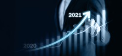 2021 business concept, business man try to predict economic by point and dragging the growth graph in year 2021 to make a benefit, profit, trend, market, success, grow up, turnover, financial,moeny