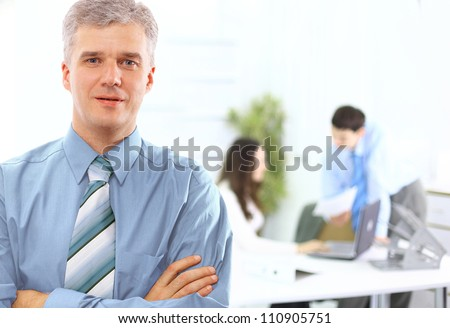 business executive - Mature business man with his colleagues in the background