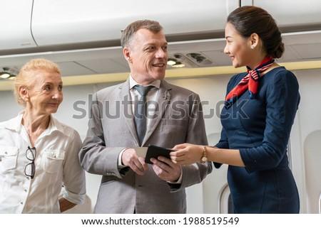 ฺBusiness male passenger and a senior female passenger bring Bording Parts to ask a flight attendant for a seat during the flight.   Photo stock ©