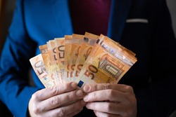 Business man's hands shows a bunch of money. Business man. Close-up of caucasian man's hands in blue jacket shows banknotes of 50 euro