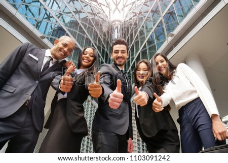 "Business people of different ethnicities dressed in suits and ties, smile and ""ok"" raising their thumbs to celebrate the team's success. Concept of: internationality and career, cooperation. #1103091242"