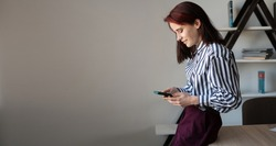 business woman is standing in the office, cheerfully rewriting text messages on modern smartphone, smiling young Caucasian woman using a mobile phone, shopping on the Internet or browsing the Interne