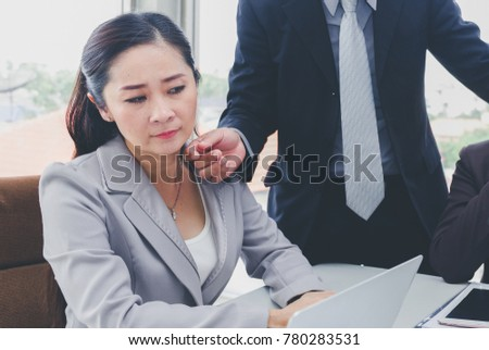 Businessman gestures or lustful with Asian business woman or Female Colleague on office. sexual harassment concept