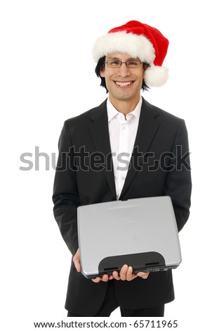 businessman holding a computer wearing a Santa hat