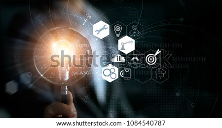 Businessman holding magnifying glass and light bulb. Idea and imagination. Creative and inspiration. Innovation icon network connection. Search engine optimization. Innovative technology industrial ストックフォト ©
