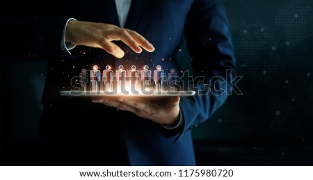 Businessman holding tablet and management group of people in his hand. Virtual icon of social network. Business technology concept.