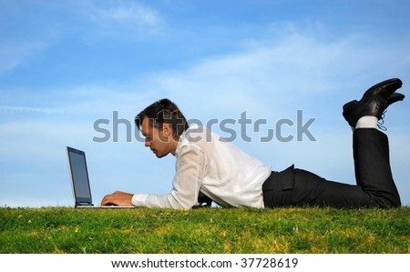 Businessman lie down and working - stock photo