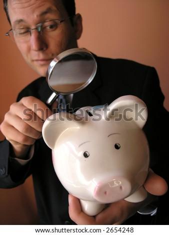 O homem de negócios olha ao banco piggy através de um vidroampliando