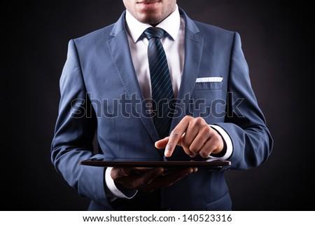Businessman working on a digital tablet against black background