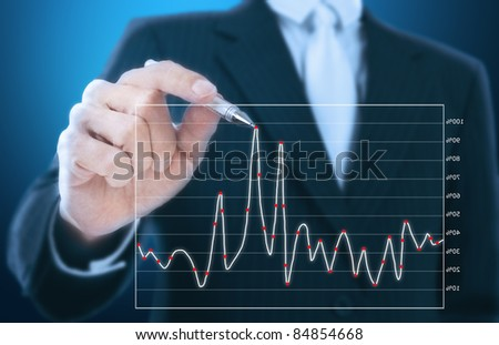 businessman writing graph of stock market - stock photo
