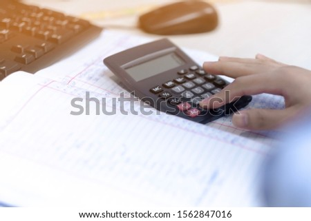 Businessmen are calculating a revenue and expense account using a calculator