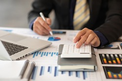 Businessmen are calculating income-expenditure and analyzing real estate investment data, Accounting Financial and tax systems concept.