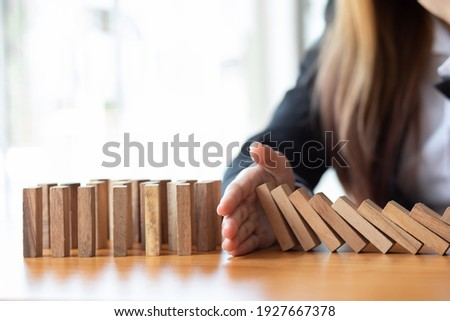 Businesswoman protect wooden block fall to planning and strategy in risk to business Alternative and prevent. Investment Insurance ,Business risk control concept, Foto stock ©